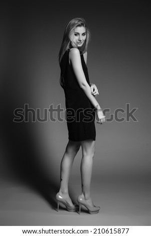 Beautiful blond woman with long hairstyle poses at studio
