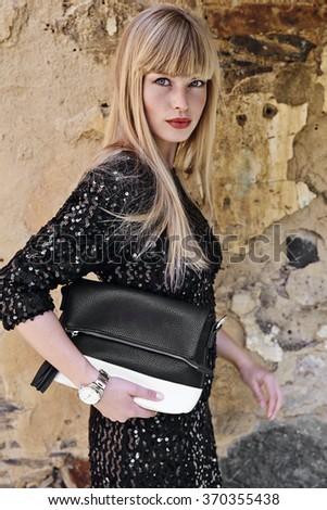 Beautiful blond woman with luxury bag, portrait - stock photo