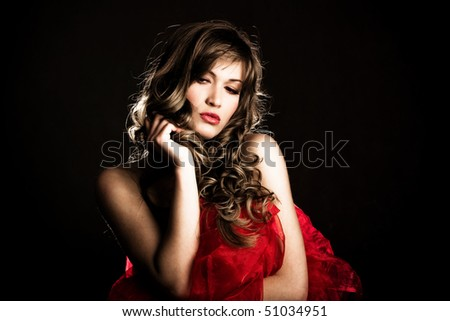 beautiful blond woman with red silky textile, studio shot