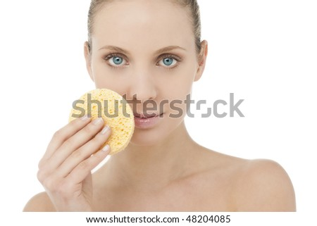 Beautiful blond woman with sponge for make-up removing