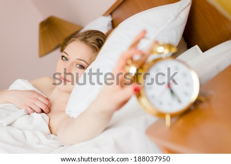 beautiful blond young business woman blue eyes girl touching alarm clock off wake up time looking at the camera smiling looking at camera - stock photo