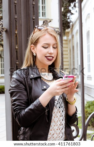 Beautiful blond young hipster girl with red lipstick and bright makeup on a sunny day outdoors. Smiling sexy woman dressed in a black leather jacket  talking on the phone