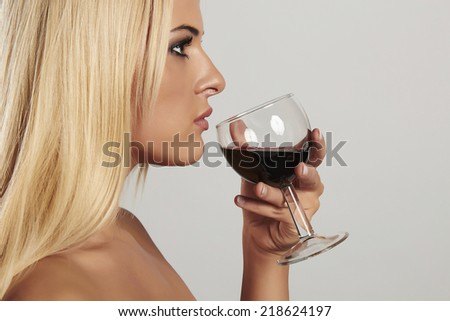 Beautiful blond young woman drinking red wine.girl with make-up.wineglass