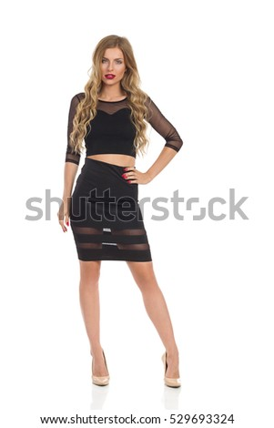 Beautiful blond young woman in black dress and beige high heels posing with hand on hip and looking at camera. Full length studio shot isolated on white.