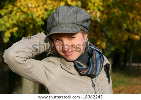 beautiful blond  young woman in cap in autumn park - stock photo
