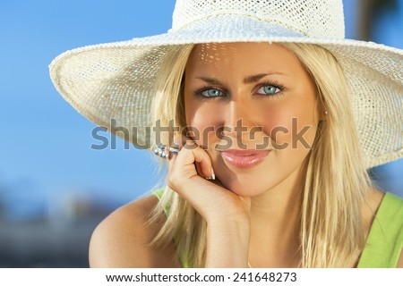Beautiful blond young woman or girl in her twenties happy smiling wearing sun hat resting on her hand in sunshine on summer day with blue sky