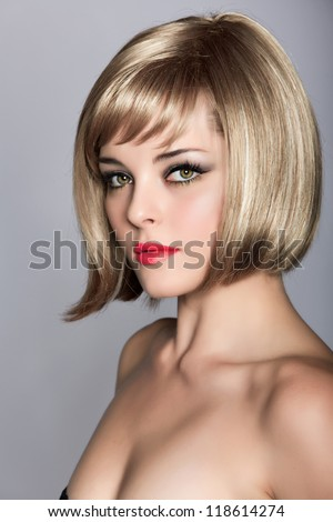 beautiful blond young woman wearing short bob hairstyle on studio background - stock photo