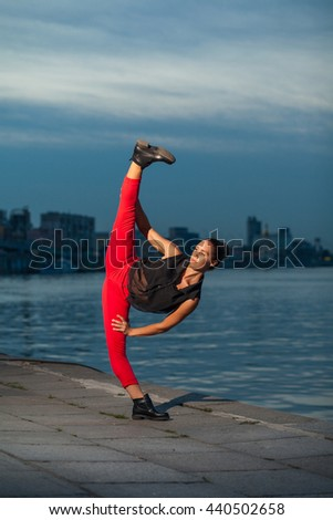 Beautiful blond young woman with black and red costume doing the splits near water.   - stock photo
