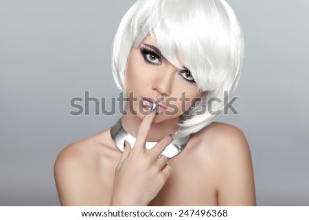 Beautiful blond young woman with polish finger. Makeup. Manicured nails. Studio photo. Girl with white Short Hair. - stock photo