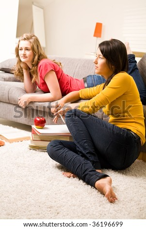 Beautiful blonde and brown teenager girls at home, speaking