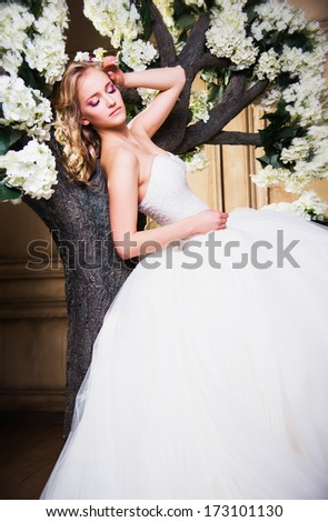 beautiful blonde bride in a luxurious wedding dress in interior - stock photo