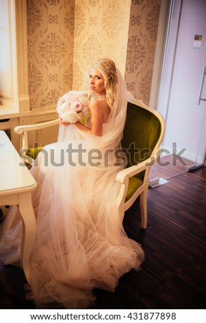 Beautiful blonde bride in elegant dress posing with bouquet on luxury chair - stock photo