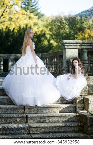 Beautiful blonde bride in sumptuous lush white dress with brunette curly little girl in nice dress posing on stone stairs with handrail background in autumn park, vertical photo - stock photo