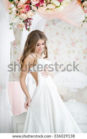 Beautiful blonde bride in the morning of the wedding day in her dress trying on wedding dress the bed with a beautiful canopy decorated with garlands of roses