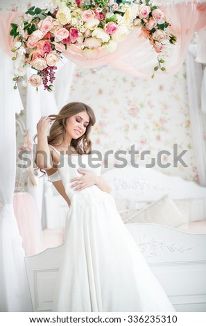 Beautiful blonde bride in the morning of the wedding day in her dress trying on wedding dress the bed with a beautiful canopy decorated with garlands of roses - stock photo