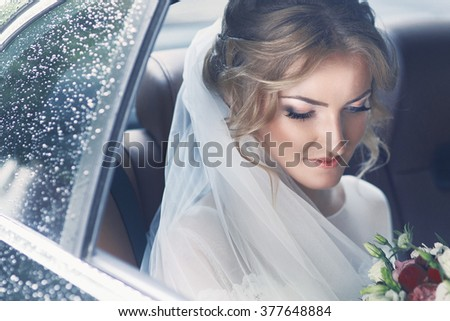 Beautiful blonde bride posing in wedding car on rainy day - stock photo