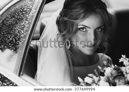 Beautiful blonde bride posing in wedding car on rainy day b&w - stock photo