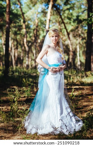 Beautiful blonde bride with wedding flowers bouquet outdoor, attractive woman in wedding dress. Happy newlywed woman  in the park. Bride with wedding makeup and hairstyle. Smiling bride. Wedding day. - stock photo