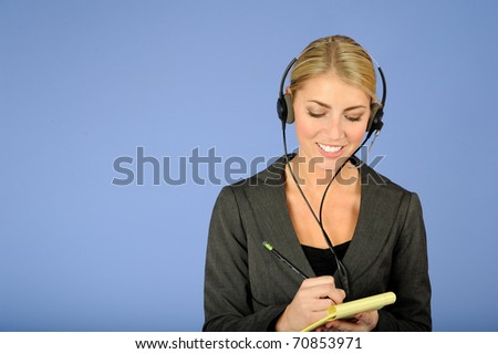 Beautiful blonde business woman in gray suit and wearing phone headphones writing on notepad - stock photo