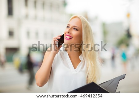 Beautiful blonde business woman on the phone at work