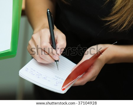 Beautiful blonde businesswoman writing on a notebook