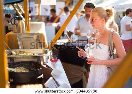 Beautiful blonde caucasian lady wearing white summer dress buying freshly prepared mealat a local food market. Urban international kitchen event taking place in Ljubljana, Slovenia, in summertime. - stock photo