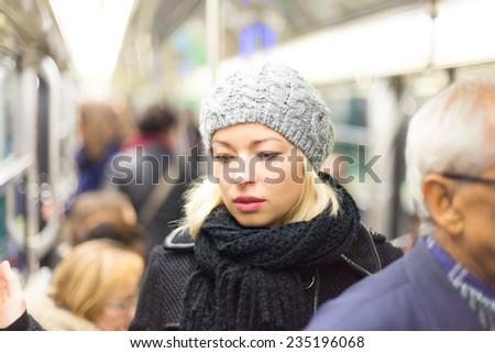Beautiful blonde caucasian lady wearing winter coat traveling by metro in rush hour. Public transport. - stock photo