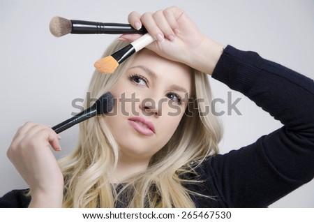 Beautiful blonde Caucasian model posing with makeup brushes - stock photo