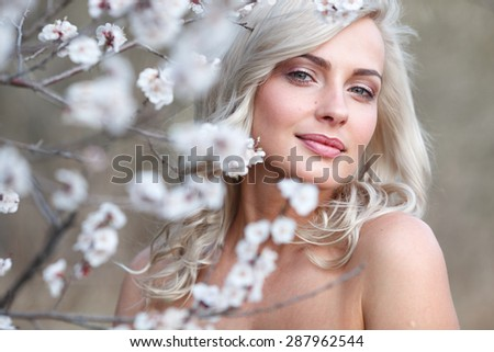 beautiful blonde closeup woman portrait in a flowered spring garden - stock photo
