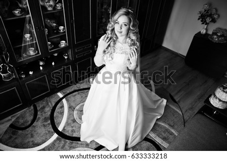Beautiful blonde curly bride at her wedding dress, preparing on room at morning.