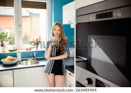 Beautiful blonde dressed in sexy short shorts drinking milk in the kitchen. The bright, modern kitchen. The girl looks at the camera. - stock photo