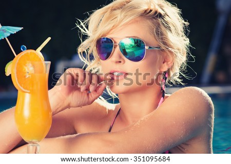 beautiful blonde enjoys in the fine afternoon, lying also the luxury pool, hot summer. girl drink fresh orange juice, slim tanned body,  thin nose  - stock photo