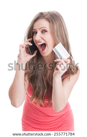 Beautiful blonde excited woman showing a credit or debit card while talking on the phone - stock photo