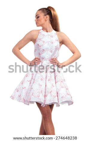 Beautiful blonde fashion woman posing with her hands around the waist while looking to her side. - stock photo