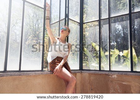 Beautiful blonde fashionable woman posing on sunny day, relaxing. - stock photo