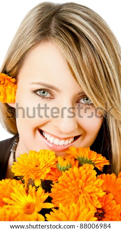 Beautiful blonde female with marigolds smiling - stock photo