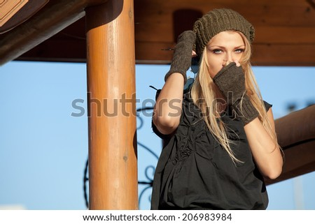 Beautiful blonde girl basking and looking into the camera near the wooden well