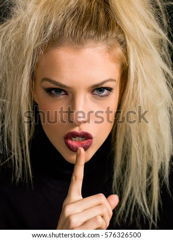 Beautiful blonde girl closeup portrait with finger on lips