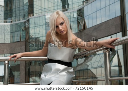 beautiful blonde girl dressed in a futuristic style against the backdrop of modern buildings