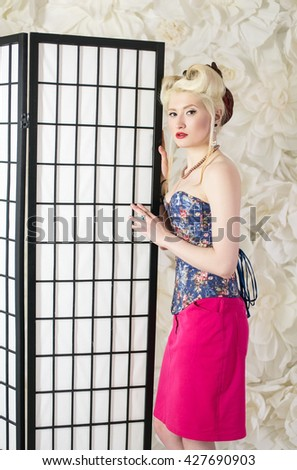 Beautiful blonde girl, dressed in the style of pin up posing near the white wall and the screen for changing clothes, fashion, beauty