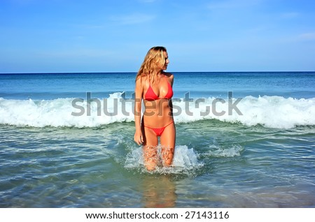 Beautiful blonde girl going out of the waving sea