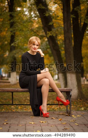 beautiful blonde girl in a black dress sitting on the bench at autumn park