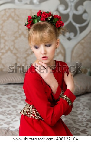 beautiful blonde girl in a red dress with a wreath of flowers on head looking to the side sitting on a bed - stock photo