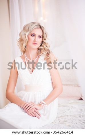 Beautiful blonde girl in a tender white dress sitting on a bed in a light boudoir, Christmas Eve