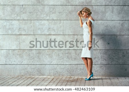Beautiful blonde girl in a white short dress with black polka dot and blue peep toe court shoes is standing beside the concrete wall. Young modern woman is standing on a gray blank background.
