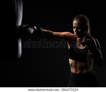 beautiful blonde girl in boxing gloves pushes the bag on a black background - stock photo