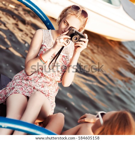 beautiful blonde girl in flower dress with photo camera takes picture of her tanned ginger girlfriend at sunset - stock photo