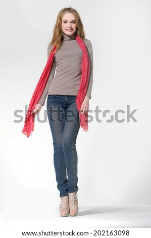 Beautiful blonde girl in jeans with scarf posing in studio - stock photo