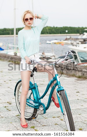 beautiful blonde girl in light summer style on city bike adjusts her hair at sea pier against yachts - stock photo