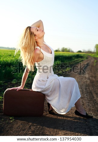 Beautiful blonde girl in long white dress, sitting on suitcase at countryside, on lonely road - stock photo